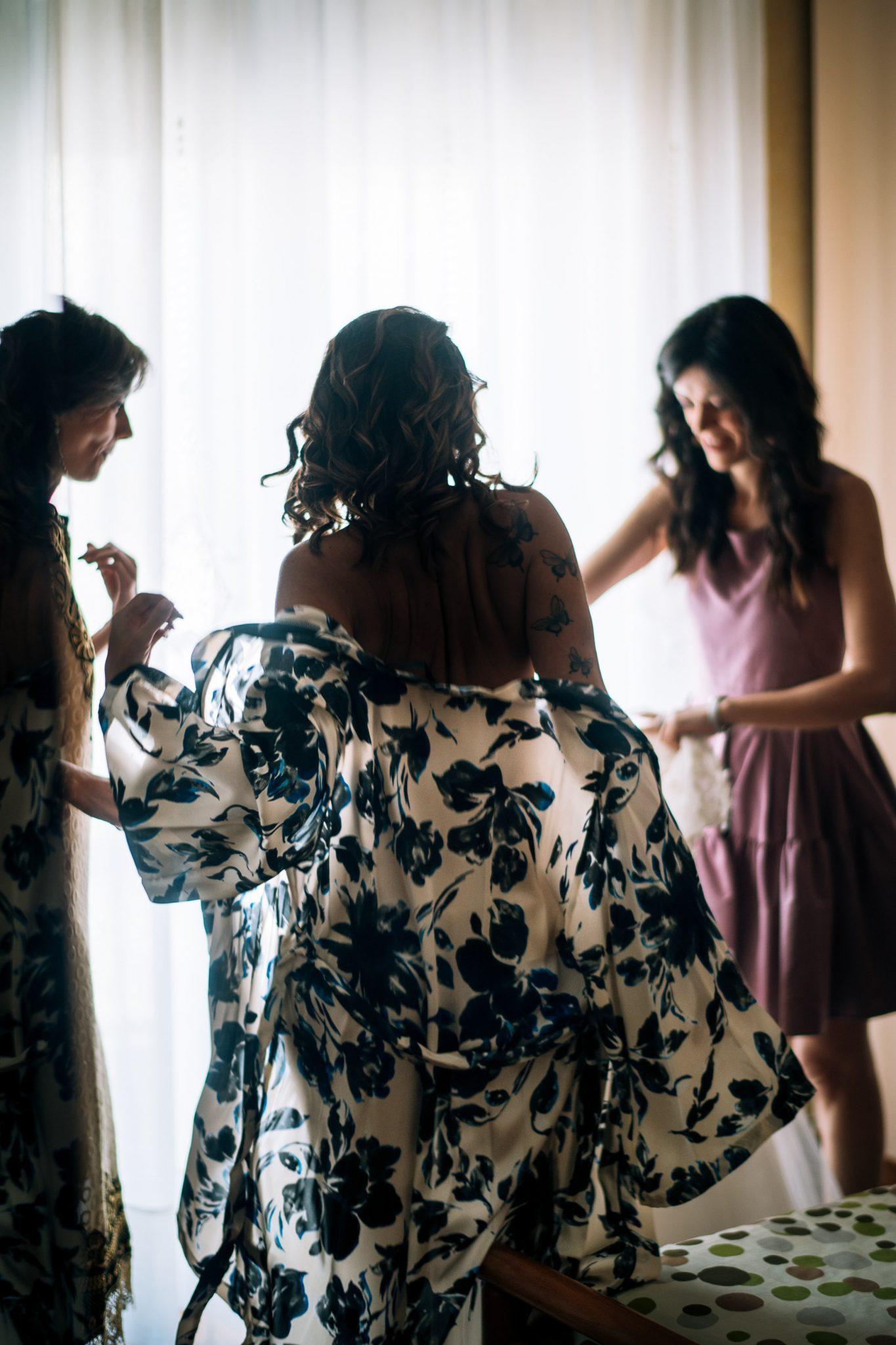 le amiche aiutano la sposa a mettersi l'abito per la cerimonia