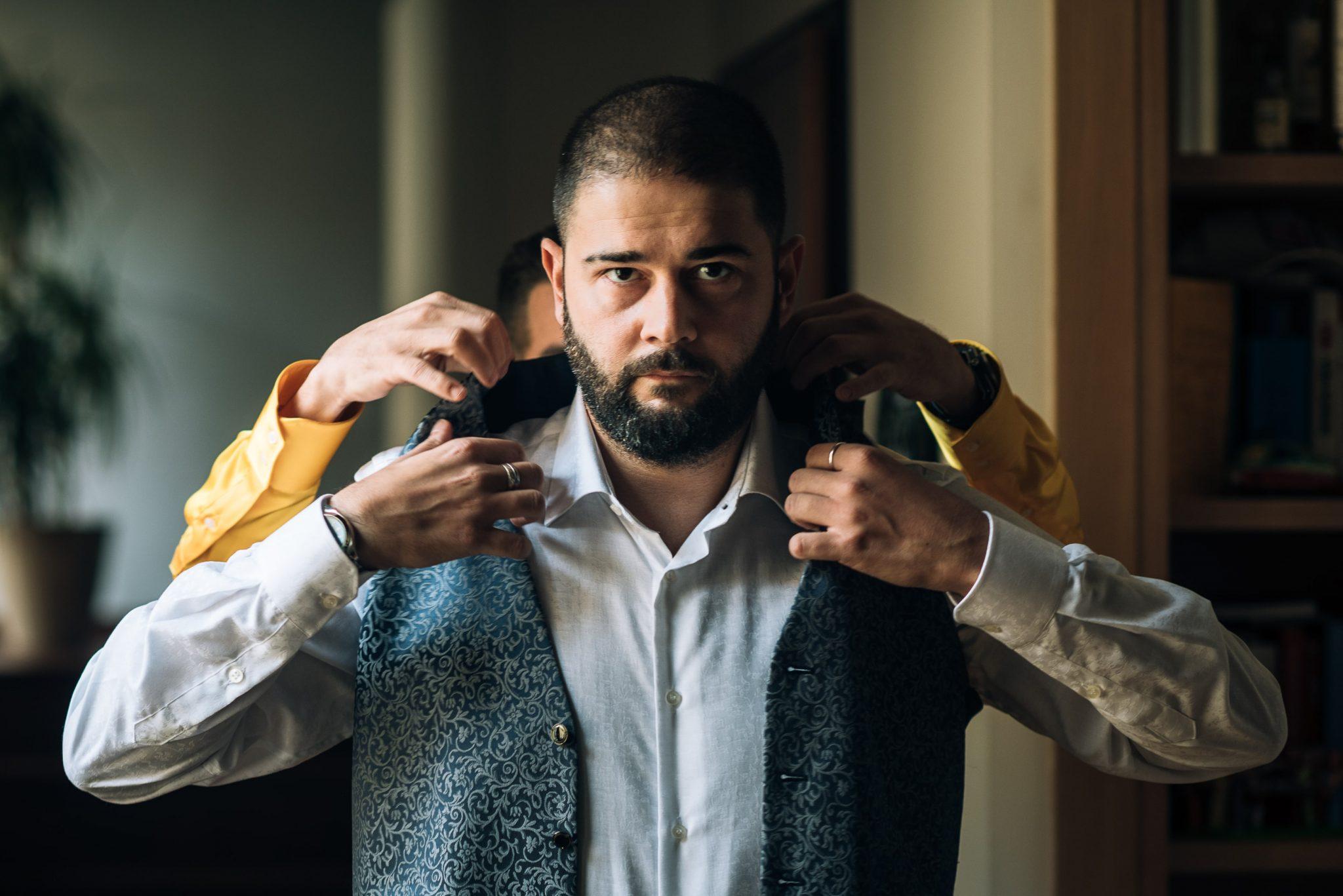 lo sposo mentre si veste in preparazione alla cerimonia nuziale