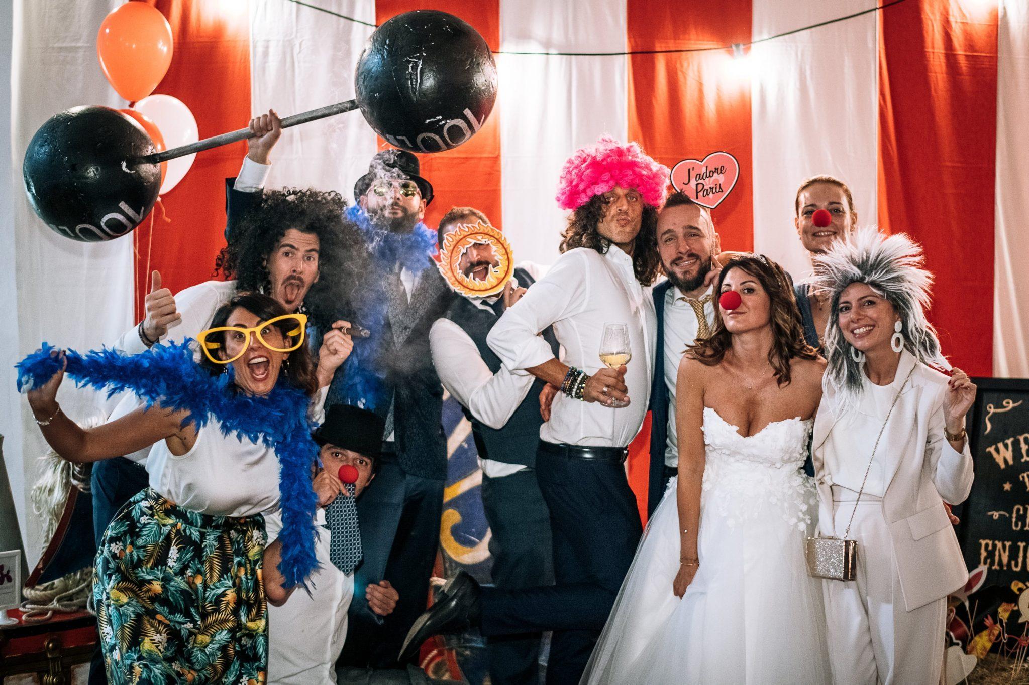 gli sposi insieme agli amici mentre si scattano una foto divertente a tema circo