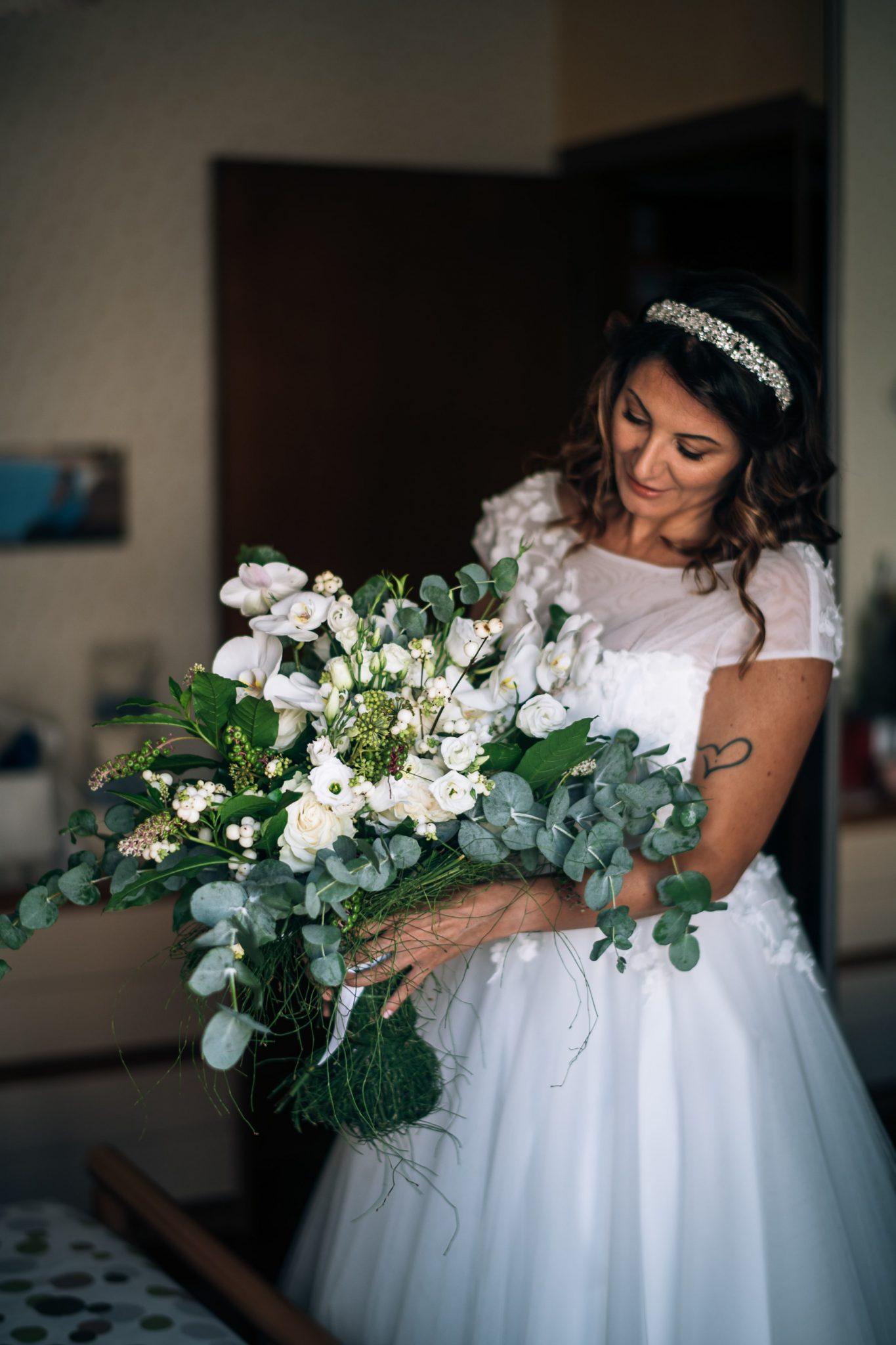 la sposa guarda sorridendo il bouquet