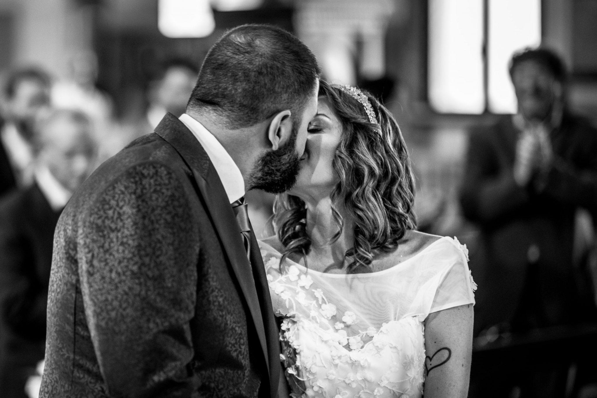gli sposi si scambiano un bacio durante la cerimonia in chiesa