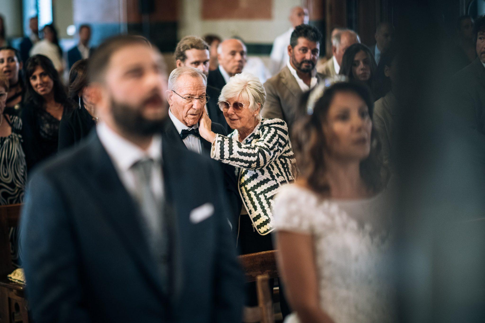 una coppia di invitati anziani si scambia una carezza durante la cerimonia