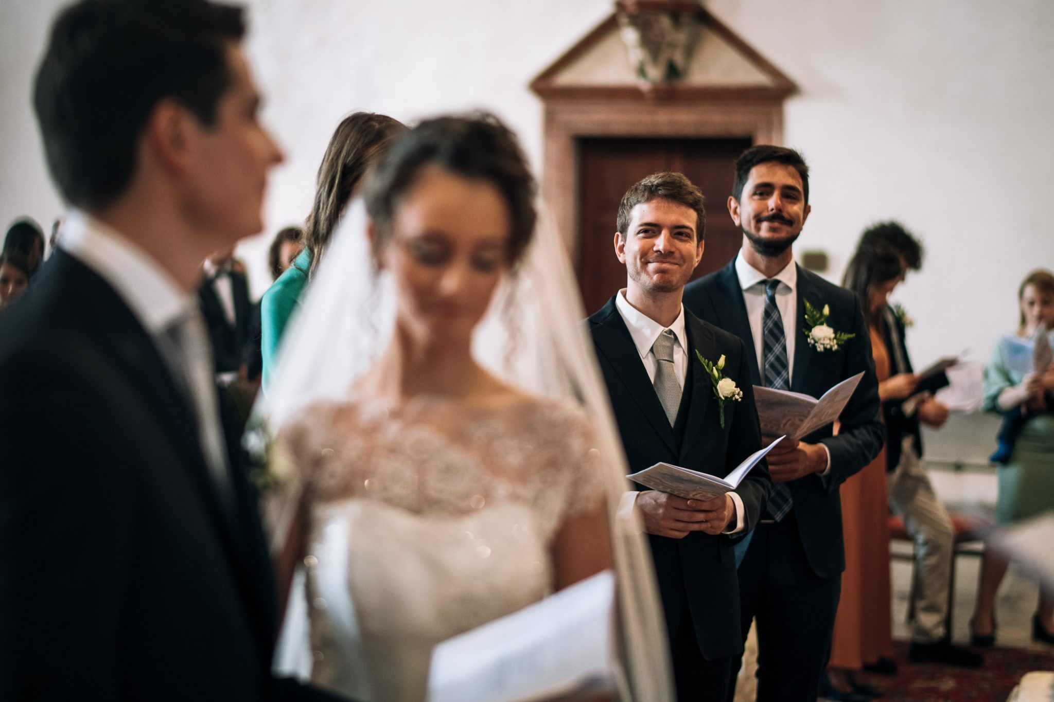 i testimoni all'altare guardano gli sposi mentre si scambiano le promesse