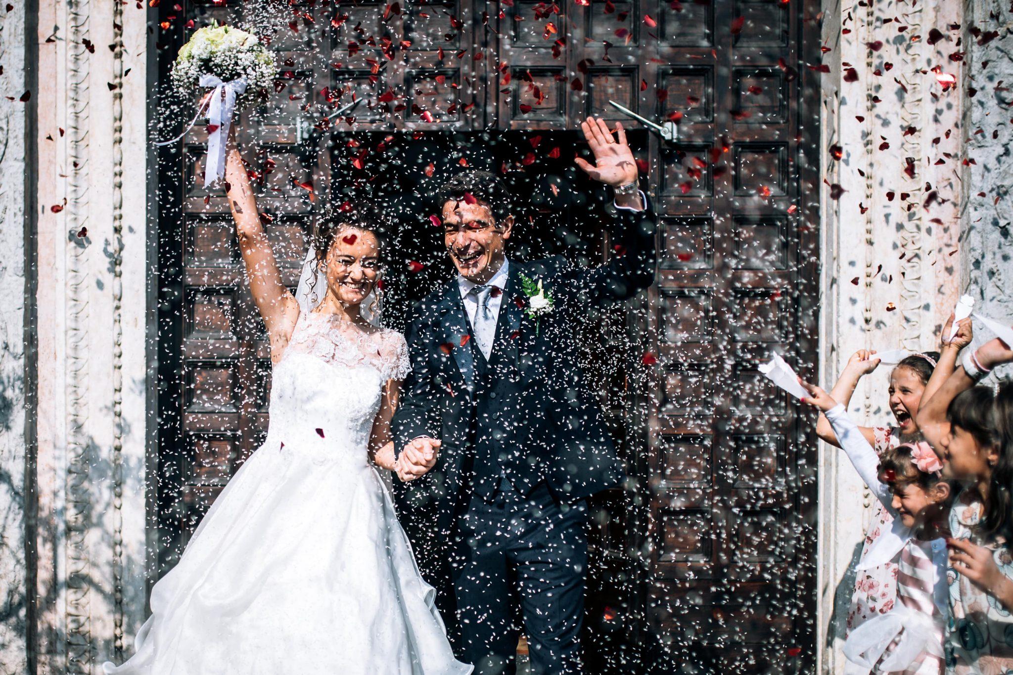 gli sposi all'uscita della chiesa con il lancio del riso e dei petali