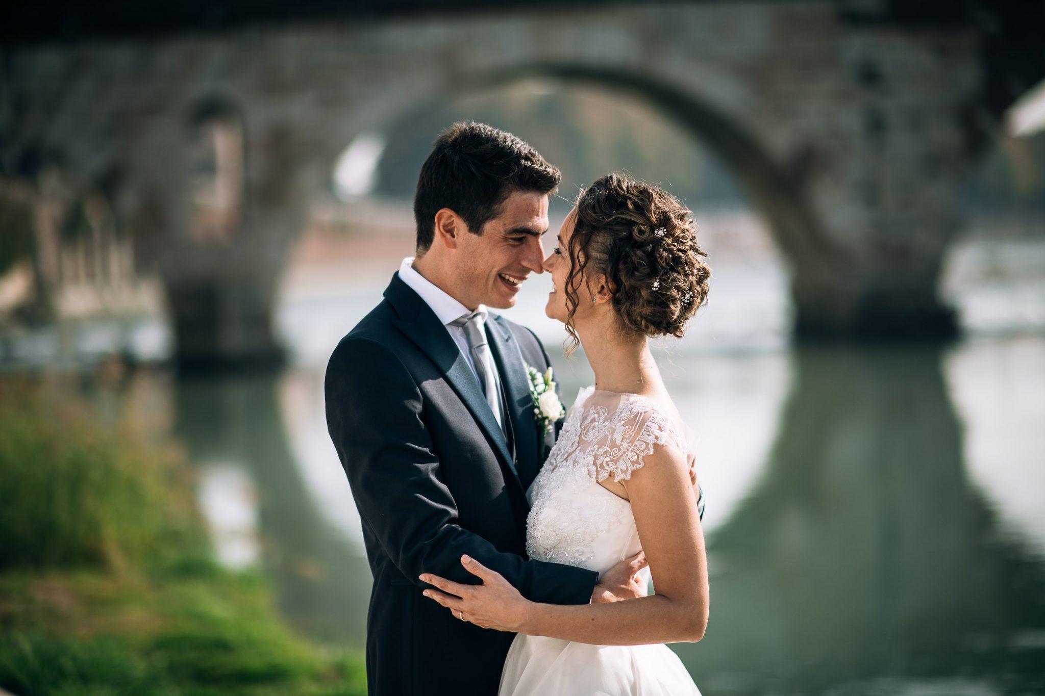 gli sposi mentre si abbracciano e guardano con il fiume alle spalle