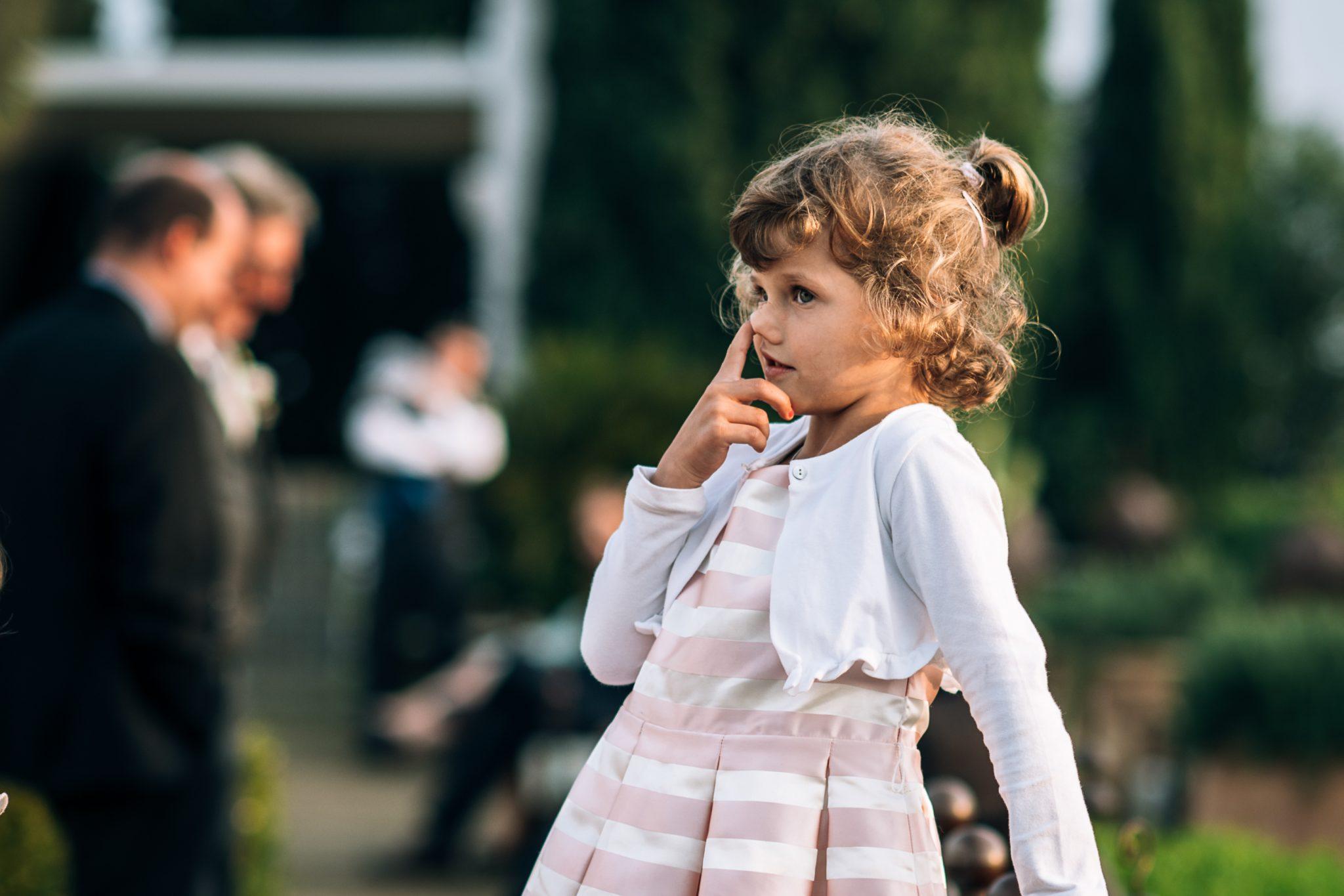 bambina invitata al matrimonio mentre si mette le mani nel naso