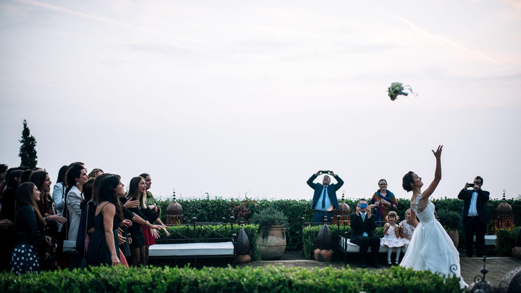 la sposa mentre lancia il bouquet con dietro le amiche
